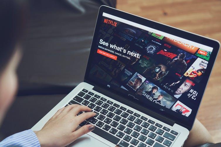 Une jeune femme devant son ordinateur regarde le menu de Netflix pour choisir un film